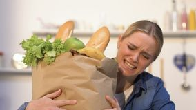 Młoda kobieta niesie ciężką papierową torbę z produktami od sklepu, potrzeby doręczeniowe zbiory
