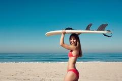 Młoda kobieta niesie surfboard przy plażą Zdjęcia Stock