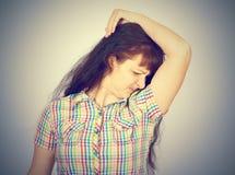 Młoda kobieta obwąchuje jej pachę, wąchający, Zdjęcie Royalty Free