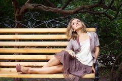 Młoda kobieta odpoczynek na ławce Obraz Stock