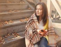 Młoda kobieta odpoczywa herbacianego obsiadanie w jesień ogródzie na krokach i pije, zawijających w woolen szkockiej kraty koc obrazy stock