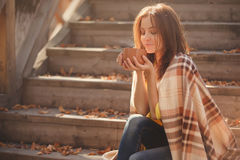 Młoda kobieta odpoczywa herbacianego obsiadanie w jesień ogródzie na krokach i pije, zawijających w woolen szkockiej kraty koc fotografia stock