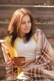 Młoda kobieta odpoczywa herbacianego obsiadanie w jesień ogródzie na krokach i pije, zawijających w woolen szkockiej kraty koc obraz stock