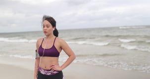 Młoda kobieta odpoczywa po jogging na plaży przy chmurną pogodą przydatność swobodny ruch zbiory
