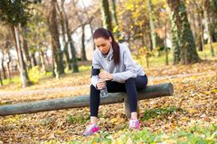 Młoda kobieta odpoczywa po jogging w parku fotografia stock