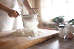 Młoda kobieta odsiewu mąka w puchar obrazy stock