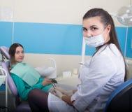 Młoda kobieta odwiedza dentysty w stomatological klinice Lekarka egzamininuje oralnego zagłębienie na zębu gniciu obraz stock