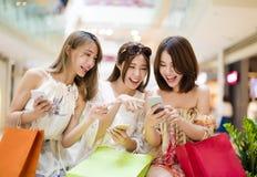 młoda kobieta ogląda mądrze telefon w zakupy centrum handlowym Obraz Stock