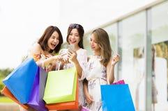 młoda kobieta ogląda mądrze telefon w zakupy centrum handlowym Zdjęcie Stock