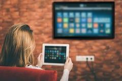 Młoda kobieta ogląda mądrze TV Zdjęcie Royalty Free