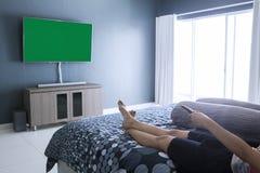 Młoda kobieta ogląda telewizję w sypialni Zdjęcie Royalty Free
