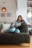 Młoda kobieta ogląda tv domową kanapę Zdjęcia Royalty Free