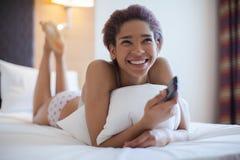 Młoda kobieta ogląda TV w pokoju kobiet piękni łóżkowi potomstwa Młody murzynki siedzenie w łóżku Obrazy Royalty Free