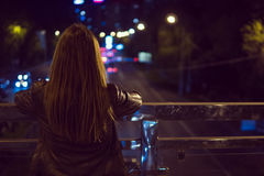 Młoda kobieta ogląda widok nocy miasta drogę od mosta Obrazy Royalty Free