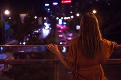 Młoda kobieta ogląda widok nocy miasta drogę od mosta obraz royalty free