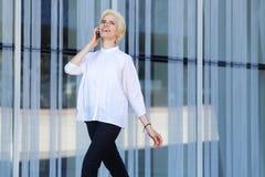 Młoda kobieta ono uśmiecha się i chodzi z telefonem komórkowym Obraz Royalty Free