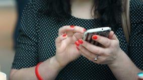 Młoda Kobieta ono uśmiecha się i texting na jej telefonie komórkowym, i zbiory wideo