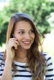 Młoda kobieta ono uśmiecha się na telefonie w parku zdjęcia stock