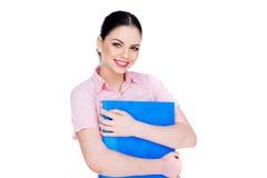 Młoda kobieta ono uśmiecha się podczas gdy trzymający błękitną falcówkę obraz stock