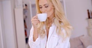 Młoda kobieta ono uśmiecha się w przyjemności cieszy się kawę Fotografia Stock