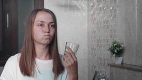 Młoda kobieta opłukuje jej usta z wodnym i patrzeje lustrem zbiory