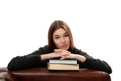 Młoda kobieta opiera na książkach fotografia stock