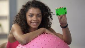 Młoda kobieta opiera na sprawności fizycznej piłce, trzyma karciany w zielonym kolorze, reklama zbiory