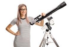 Młoda kobieta opiera na teleskopie fotografia stock