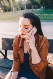 Młoda kobieta opowiada i słucha na mądrze telefonu mądrze telefonie w miasto parka obsiadaniu na ławce z zakończeń oczami fotografia royalty free
