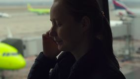 Młoda kobieta opowiada na telefonie komórkowym przed dużym okno przy lotniskiem zbiory wideo