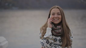 Młoda kobieta opowiada na telefonie komórkowym uśmiechniętym i śmia się dyskutujący niektóre zagadnienie z istnym interesem zbiory