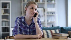 Młoda Kobieta Opowiada na telefonie podczas gdy Relaksujący na krześle zbiory