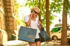Młoda kobieta opowiada na telefonie na ulicie z torbami zdjęcia stock