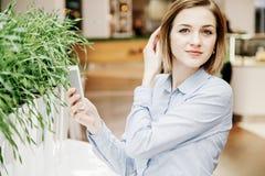 Młoda kobieta opowiada przez telefonu Dziewczyna siedzi przy stołem i robi rozkazowi kobieta jednostek gospodarczych Zdjęcie Royalty Free
