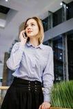 Młoda kobieta opowiada przez telefonu Dziewczyna siedzi przy stołem i robi rozkazowi kobieta jednostek gospodarczych Zdjęcie Stock