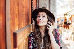 Młoda kobieta opowiada przy cel z kapeluszem obok starego drewnianego drzwi zdjęcia stock