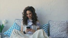 Młoda kobieta opowiada z chłopakiem na jej telefonie komórkowym po budzić się up zbiory