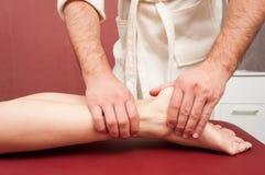 Młoda kobieta otrzymywa noga masaż masażystą Fotografia Stock
