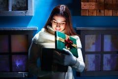 Młoda kobieta otwiera jej prezentów boże narodzenia w magicznej atmosferze Zdjęcie Stock