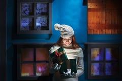 Młoda kobieta otwiera jej prezentów boże narodzenia w magicznym domu Fotografia Stock