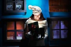 Młoda kobieta otwiera jej prezentów boże narodzenia w magicznym i kolorowym h Zdjęcie Royalty Free