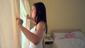 Młoda kobieta otwiera jej sypialni zasłony w ranku zbiory