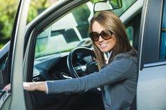 Młoda kobieta otwiera samochodowego drzwi Obraz Royalty Free