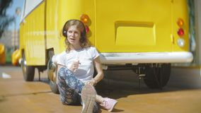 Młoda kobieta outdoors żółtego furgonu samochodową słuchającą muzyką w hełmofonach używać smartphone - relaksować, cieszy się, po zdjęcie wideo