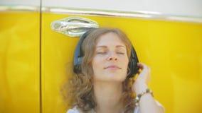 Młoda kobieta outdoors żółtego furgonu samochodową słuchającą muzyką w hełmofonach używać smartphone - relaksować, cieszy się, po zbiory
