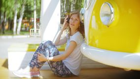 Młoda kobieta outdoors żółtego furgonu samochodową słuchającą muzyką w hełmofonach używać smartphone - relaksować, cieszy się, po zbiory wideo