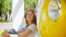 Młoda kobieta outdoors żółtego vagon samochodową słuchającą muzyką w hełmofonach używać smartphone - relaksować, cieszy się, poję zbiory