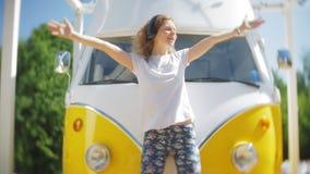Młoda kobieta outdoors żółtego vagon samochodową słuchającą muzyką w hełmofonach używać smartphone - relaksować, cieszy się, poję zdjęcie wideo
