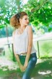 Młoda kobieta outdoors w białej koszulce i cajgach, z jaskrawym makeup, czerwone wargi Obrazy Stock
