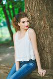 Młoda kobieta outdoors w białej koszulce i cajgach, z jaskrawym makeup, czerwone wargi Patrzeć kamerę Fotografia Royalty Free